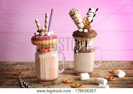Milkshake, donuts and other sweets in jars on wooden table