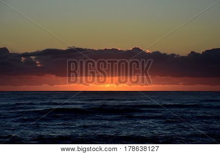 Beautiful sunrise cloudscape over ocean background. Sun rays beaming through picturesque clouds above sea. Blue sky with clouds sea and sun on the horizon. Beautiful sunrise over the quiet calm sea.