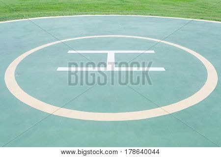 Close - up empty helipad and green grass