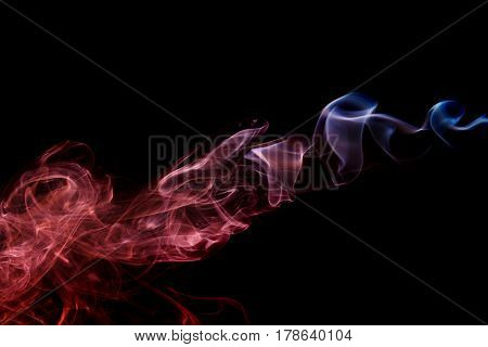 Abstract art. Color red blue smoke from the aromatic sticks on a black background. Background for Halloween. Texture fog. Design element. The concept of aromatherapy.