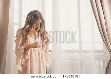 Young cute housewife at the window. Girl in sexy gown. Good morning. Soft focus.