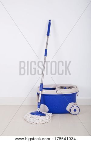 Mop And Blue Bucket On Floor And Wall Background