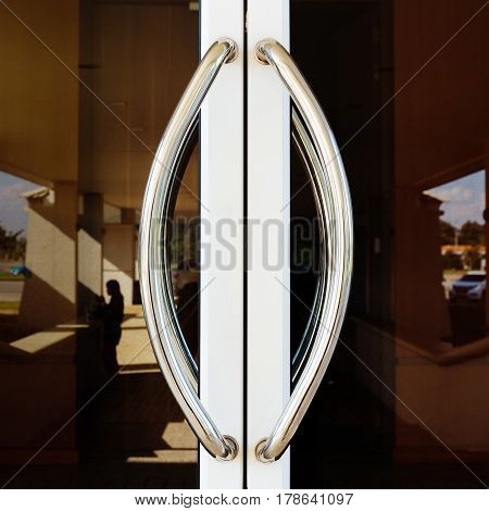 Chrome door handle and glass of aluminium door outside building.