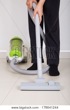 Woman Legs With Vacuum Cleaner Cleaning Floor