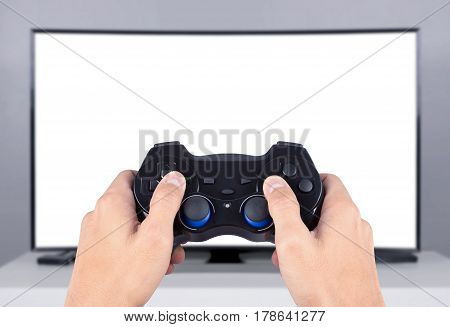hand holding joystick to playing video game on the tv (blank screen)