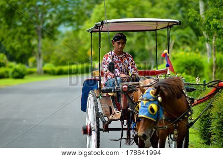 Magelang, Central Java, Indonesia - Circa January 2012 - A shot of an unidentified man riding on a horse carriage in Borobudur compound