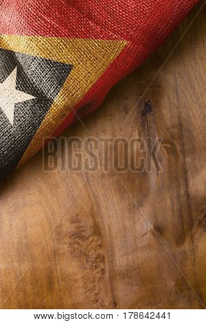 Flag of East Timor state on a wooden background.