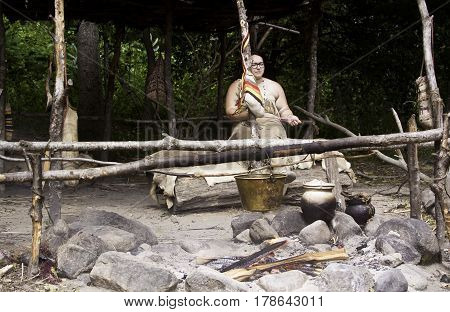Plimoth Plantation, Plymouth, Massachusetts - September 10, 2014 - Wide view of a Wampanoag Indian woman working yarn for weaving in front her work fire heating a cauldron and bucket in the Wampanoag Indian Village at Plimoth Plantation with foliage