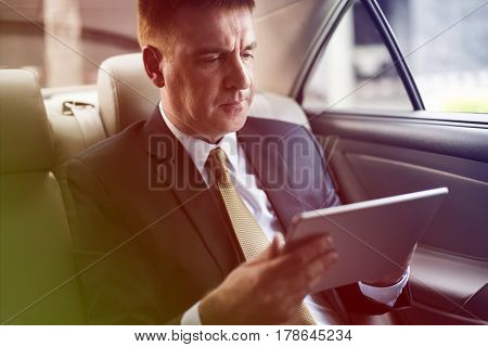 Businessman using digital tablet on backseat of the car