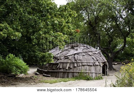 Wide view of a Wampanoag Indian hut made of branches and covered in bark in the Wampanoag Indian Village at Plimoth Plantation, Plymouth, Massachusetts surrounded by trees and foliage on a bright sunny day in September.
