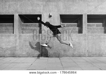 Young man jumping in front of university campus building