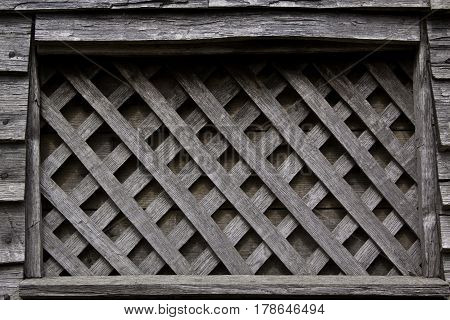 Close up of very old weathered lattice wood pattern excellent background or texture at Plimoth Plantation, Plymouth, Massachusetts on a bright sunny day in September.