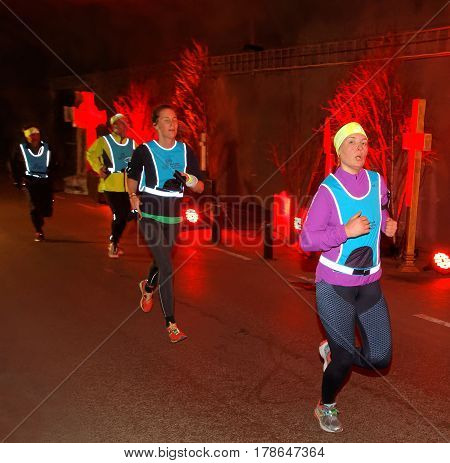 STOCKHOLM SWEDEN - MAR 25 2017: Group of runners in a tunnel with red light and grave stones the Stockholm Tunnel Run Citybanan 2017. March 25 2017 in Stockholm Sweden