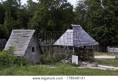 Wide view of an old gray wooden shed beside an old wood roofed kiln in the pilgrim village at Plimoth Plantation, Plymouth, Massachusetts, with trees and foliage in the background on an overcast but bright day in September.
