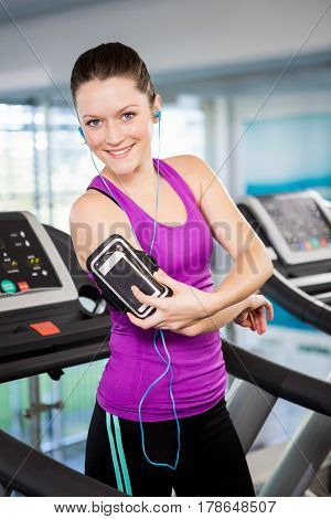 Smiling woman on treadmill using smartphone at the gym