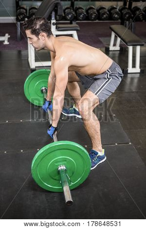Shirtless man lifting barbell in the gym