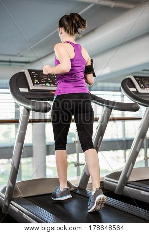 Fit woman running on treadmill at the gym