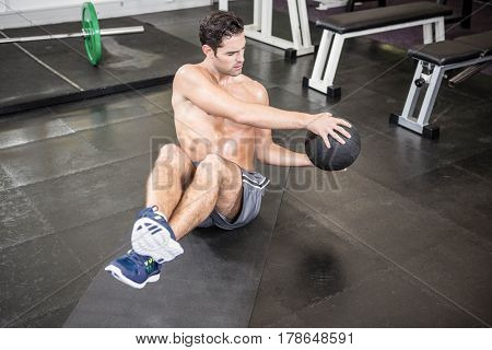 Shirtless man exercising with medicine ball at the gym