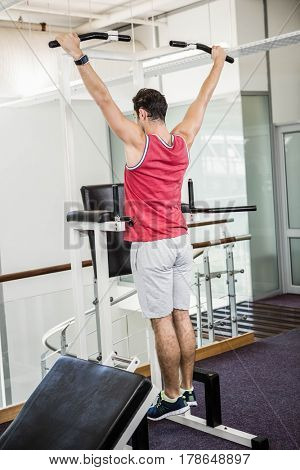 Muscular man doing pull up in a gym