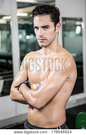 Serious shirtless man with arms crossed in the gym