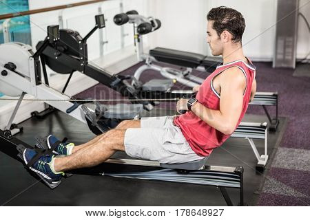 Muscular man on rowing machine at the gym