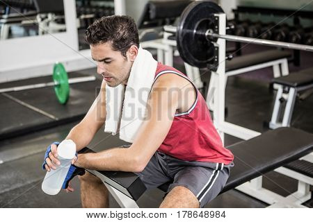 Tired man sitting on bench holding bottle of water in the gym