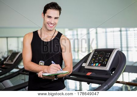 Smiling man on treadmill writing on clipboard at the gym