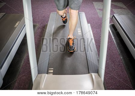Lower section of man running on treadmill at the gym