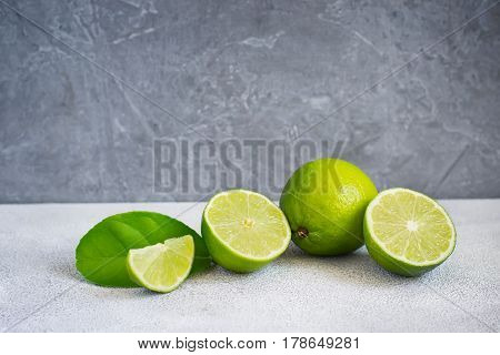 Limes are whole and halves on a gray background copy space.