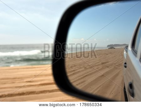 Reflections in a side view mirror of a car driving on the beach. Rear view car mirror. Concept of 4wd off-road driving in the nature.
