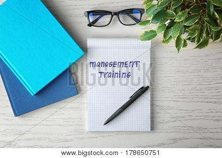 Notebook with written text MANAGEMENT TRAINING, pen and eyeglasses on table