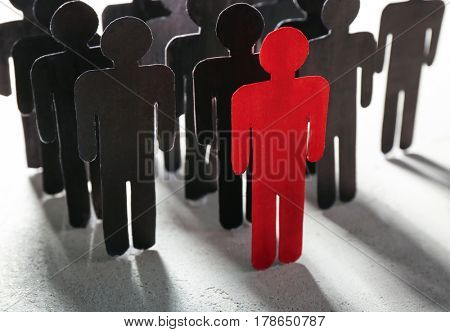 Boss vs leader concept. Crowd of human figures behind red one on light background
