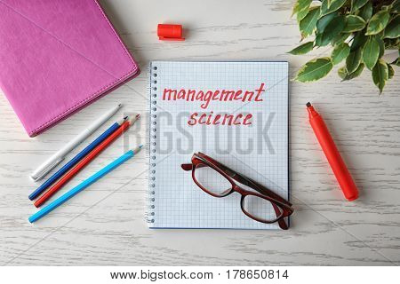 Notebook with written text MANAGEMENT SCIENCE, eyeglasses and stationery on table