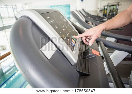 mans hand setting treadmill in the gym