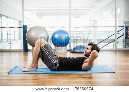 Muscular man doing abdominal on mat in the studio