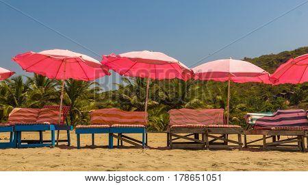 Beach chairs and with umbrella on the beach near Sweet lake Arambol beach North Goa India
