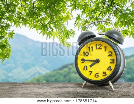 Closeup black and yellow alarm clock for decorate show a quarter to eight o c'clock or 7:45 a.m. on blurred leaves and mountain view background