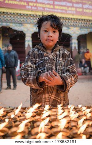 KATHMANDU, NEPAL - DEC 18, 2015: Unidentified small boy prayer near Boudhanath Stupa in Kathmandu, Nepal., Boudhanath is one of the largest ancient stupa in the world
