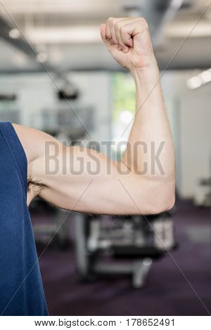 Close up of man showing biceps at the gym