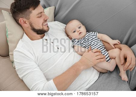 Father lying with cute baby daughter on sofa at home