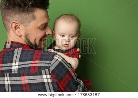 Father posing with cute baby daughter on color background