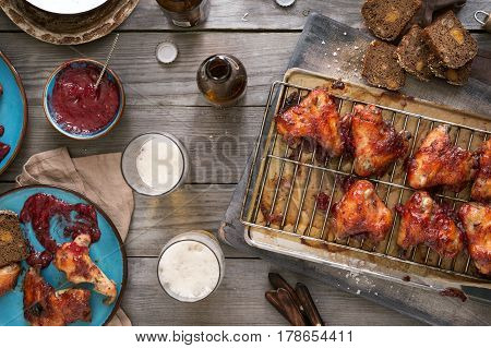Chicken wings in cranberry sauce with lager beer on rustic wooden table top view