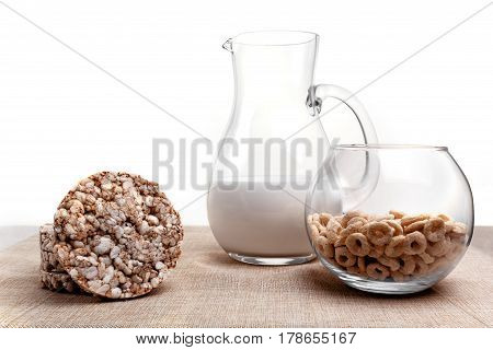 puffed wheat, corn and milk jug rings on the tablecloth from a sacking. Isolated