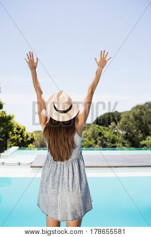 Rear view of brunette raising hands by the pool