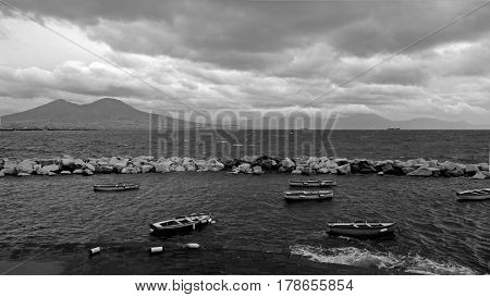 Restless Bay of Naples overlooking the Vesuvius and the beautiful boats in the foreground. Black and white frame