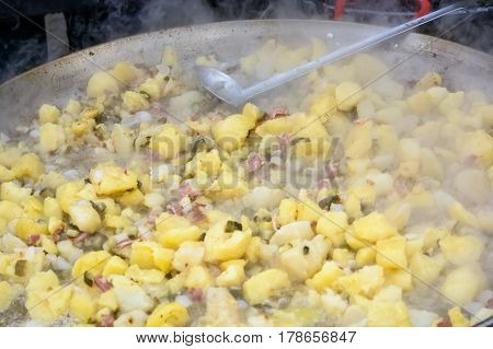 Close up of fried potatoes in an iron pan