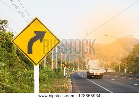 Turn right road sign on country road with sunlight