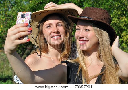two teenage girls in cowboy hats taking selfie in the summer day