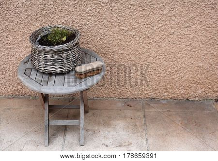 Vintage things:old French garden wooden folding table, wicker basket with flowers, old shoe brush with stiff bristles, background - yellow pink walls. Provence. France