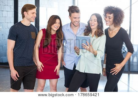 Colleagues looking in digital tablet and laughing at office